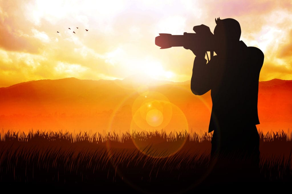 Silhouette of a photographer taking picture of beautiful landscape during sunrise